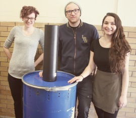 Students stand with the pyrolysis unit they prototyped