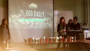 The group presents their project, with a lineup of disposable mugs in front of them on the desk